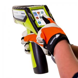 Des mains avec des gants touchent l'écran tactile de l'analyseur